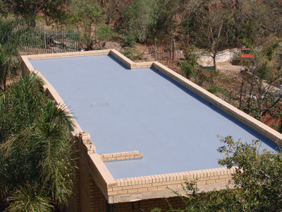 Flat concrete roof withstands strong winds for Concrete flat roof house plans