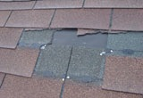 Wind damaged roof shingles